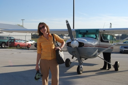 happy-woman-standing-front-of-plane.jpg